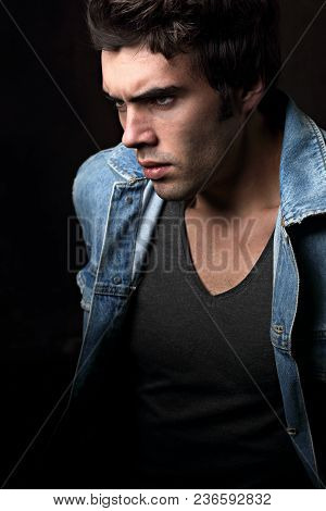 Sexy Serious Angry Male Model Profile  In Blue Jacket On Dark Shadow Background. Fashion Style Contr