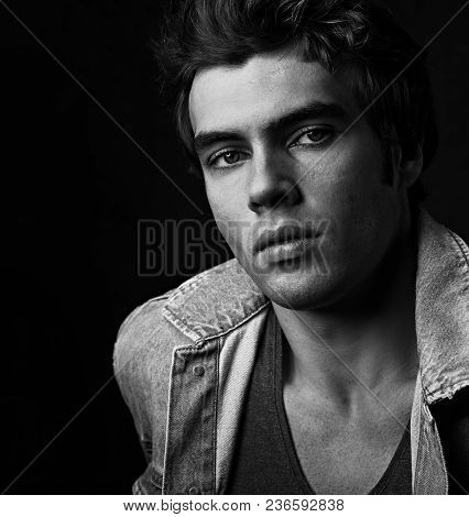 Sexy Serious Male Model Posing In Blue Jacket On Dark Shadow Background. Fashion Style Contrast Vogu