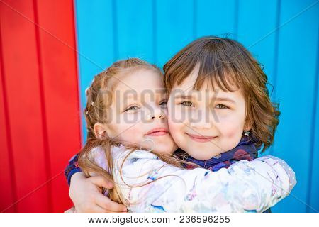 Happy Little Girlfriends Embrace Outdoor. Colourful Background