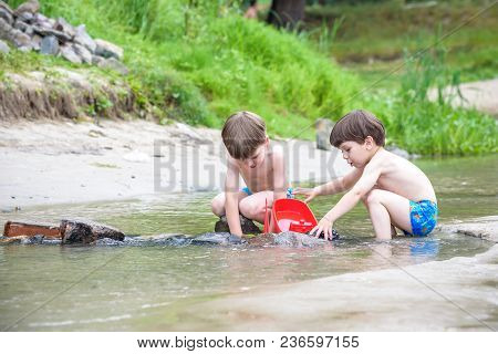 Two Blond Brothers Are Having Fun On The Beach In A Sunny Summer Day