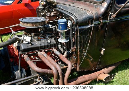 A Street Rod Exposing The Engine, Manifold, And Exhaust System Are Exposed On A Hoodless Car.