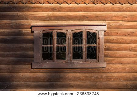 Log Wall With One Centered Rectangular Window Under Sunlight With Blurry Shadows