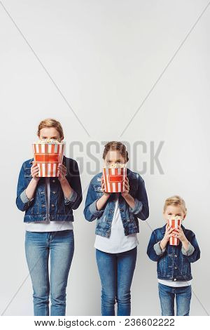 Obscured View Of Family In Similar Denim Clothing Covering Faces With Popcorn Isolated On Grey