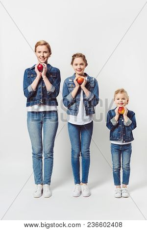 Smiling Mother And Daughters Of Different Generations In Similar Clothing With Fresh Apples Isolated