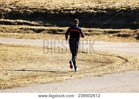 A Man Of Age Runs Around The Path, Taking Part In Sports.
