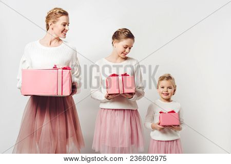 Smiling Mother And Little Daughters In Similar Pink Tutu Tulle Skirts With Wrapped Gifts Isolated On