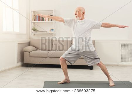 Sporty Elderly Guy Practicing Yoga Indoors. Senior Man Doing Stretching Exercise At Home. Active Lif