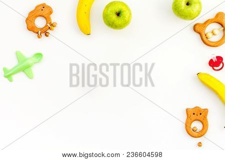 Healthy Nutrition For Babies. Apple, Banana Near Toys On White Background Top View.
