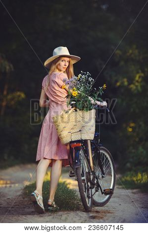 Beautiful Girl Wearing A Nice Pink Dress Having Fun In A Park With A Bicycle Holding A Beautiful Bas