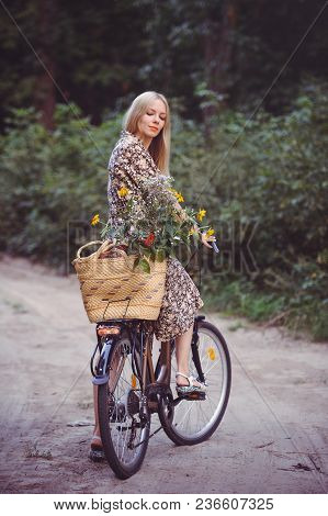 Beautiful Girl Wearing A Nice Dress Having Fun In A Park With A Bicycle Holding A Beautiful Basket W