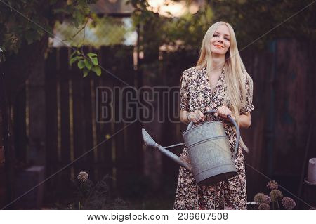 Beautiful Young Woman In A Studded Summer Dress On A Background Of A Garden With A Watering Can In H