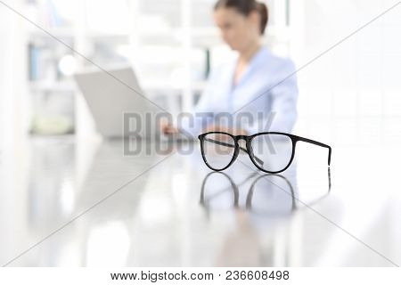 Eyeglasses Leaning On Desk And Woman Working On Computer At Office In Background