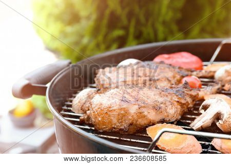Appetizing juicy spare ribs and vegetables on barbecue grill outdoors, close up