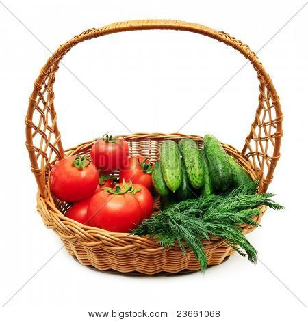 Tomatoes and cucumbers in a basket isolated on a white background.