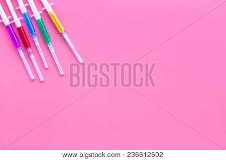 Vaccination, Immunization. Syringe With Colored Medicament On Pink Background Top View.