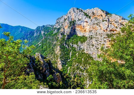 Steep picturesque cliff in the French Alps. The fascinating journey to the most beautiful canyon in Europe - Verdon. Concept of ecological, extreme and active tourism
