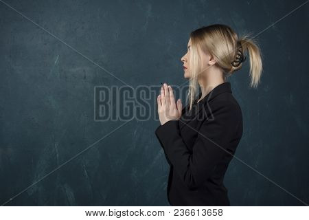 Portrait In A Profile Of A Beautiful Woman Folded In Front Of Her Hands In A Black Suit Against A Bl
