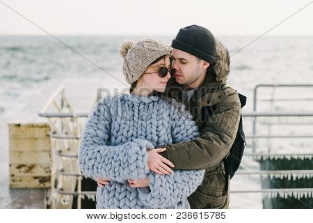 young boyfriend hugging his stylish girlfriend in merino sweater on winter quay poster