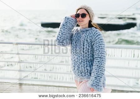 stylish young girl in sunglasses and merino wool sweater on winter quay poster