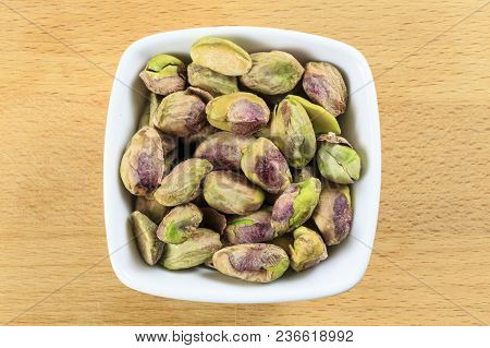 Overhead Shot Of Pistachio Nuts (no Shell) In A White Bowl On A Wooden Board Background. Pistachio N