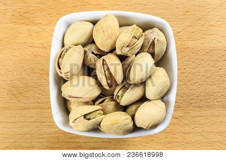 Overhead Shot Of Shelled Pistachio Nuts In A White Bowl On A Wooden Board Background. Pistachio Nuts