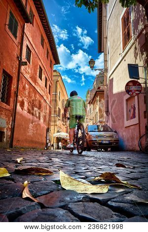 Rome, Italy - May 17, 2017: Generic Picturesque Roman Architecture And A Man Riding A Bike On The St