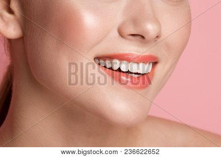 Close Up Of Laughing Beautiful Woman Lips Painted With Nude Gloss. Her Teeth Are Healthy And White.