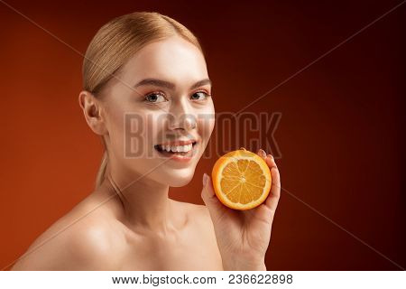 Vitality Concept. Portrait Of Young Groomed Lady Looking At Camera While Demonstrating Half Of Fresh