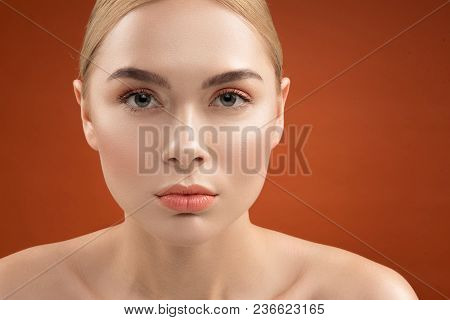 Close Up Portrait Of Serious Woman Face With Young Groomed Skin And Light Maquillage. She Is Looking