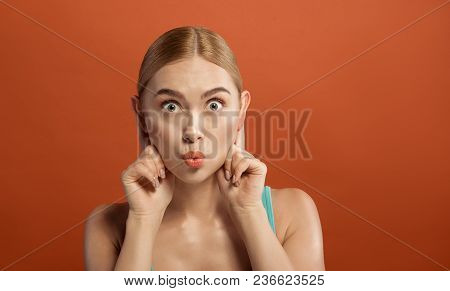 Portrait Of Attractive Woman With Amusing Grimace. She Is Staring At Camera And Doing Ears Lop-eared