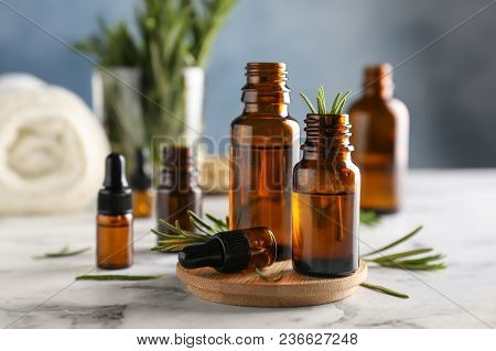 Bottles With Rosemary Essential Oil On Table