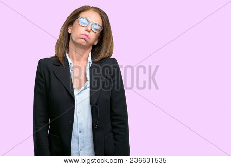 Middle age business woman with sleepy expression, being overworked and tired