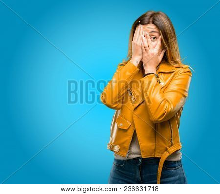 Beautiful young woman smiling having shy look peeking through her fingers, covering face with hands looking confusedly broadly, blue background