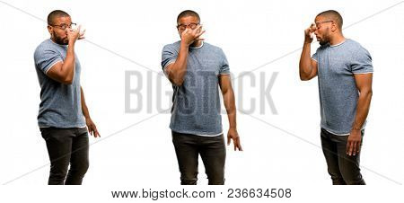 African american man with beard with sleepy expression, being overworked and tired, rubbes nose because of weariness