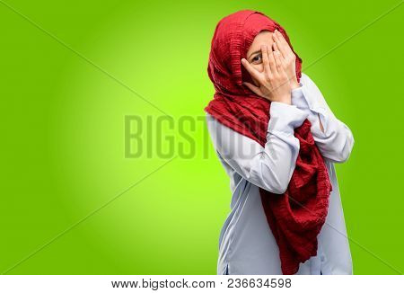 Young arab woman wearing hijab smiling having shy look peeking through her fingers, covering face with hands looking confusedly broadly