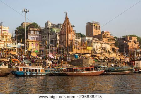 VARANASI, INDIA - MAR 26, 2018: View from a boat glides through water on Ganges river along shore of Varanasi. According to legends, the city was founded by God Shiva about 5000 years ago.