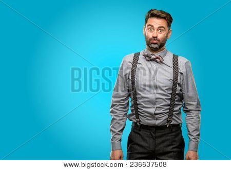 Middle age man, with beard and bow tie puffing out cheeks, having fun making funny face