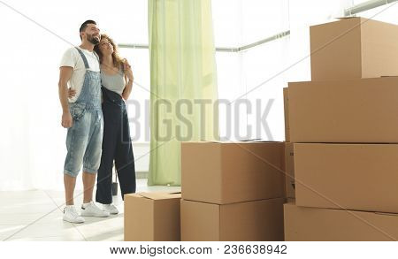 Happy young couple standing in new apartment