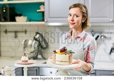 Portrait of attractive Caucasian woman standing in kitchen near decorated appetizing cake and smiling at camera