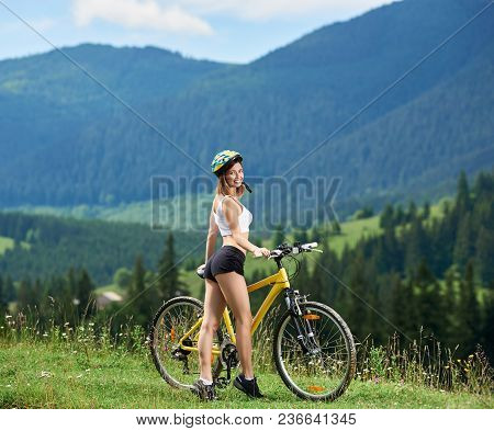 Attractive Young Woman Cyclist Standing Near Yellow Bicycle On A Rural Trail In The Mountains, Weari