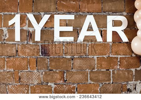 Arranged White Letters Saying One Year On Shabby Brick Wall With Balloons Near.