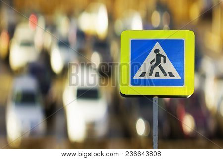 Road Sign Pedestrian Crossing On The Night On The Background Cars.