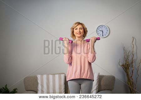 Happy Senior Woman Making Fitness Training With Dumbbells At Home.