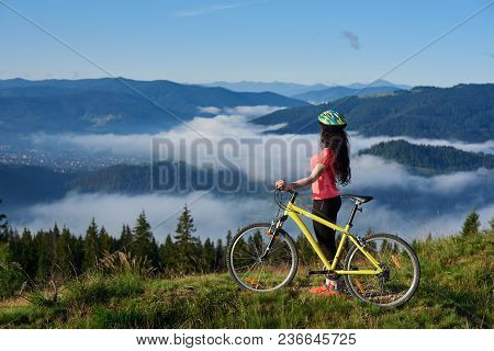 Side View Of Sporty Female Biker With Yellow Bicycle In The Mountains, Wearing Helmet And Red Red T-