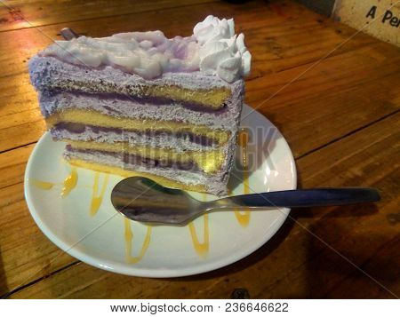 Taro Cake Layer Of Cake And Whip Cream Cover. Decorate White Plate With Caramel In Light Warm Tone.