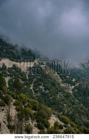 A Highway Passes Through A Mountain As A Storm And Heavy Fog Rolls In