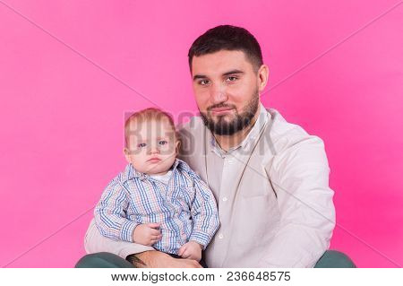 Happy Father With A Baby Son Isolated On A Pink Background.