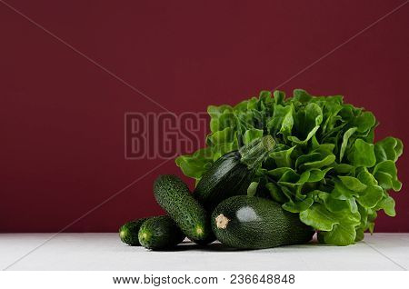 Green Summer Vegetables On White Wood Board And Bordo Kitchen Wall. Modern Elegant Colorful Concept