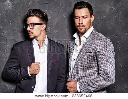 portrait of two sexy handsome fashion male models men dressed in elegant suits posing near dark  gra