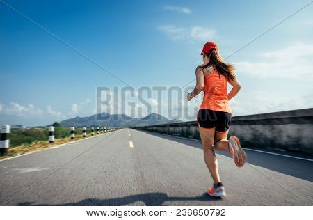 An Asian Woman Athletic Is Jogging On The Concrete Road, She Is Warming Her Body And Tideten Her Tyi